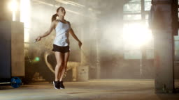Athletic Beautiful Woman Exercises with Jump / Skipping Rope in a Gym. She's Covered in Sweat from Her Intense Cross Fitness Training.