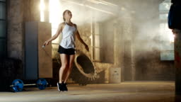 Athletic Beautiful Woman Exercises with Jump / Skipping Rope in a Gym. She's Doing Part of Her Intense Fitness Training.
