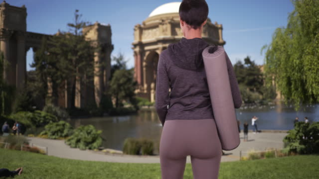 vídeos de stock e filmes b-roll de athletic black woman with yoga mat in park waiting for class to start - san francisco