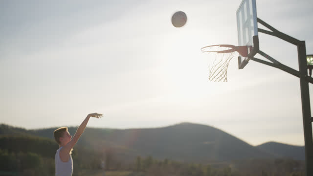 athletic boy plays basketball and shoots many baskets by himself - one teenage boy only stock videos & royalty-free footage
