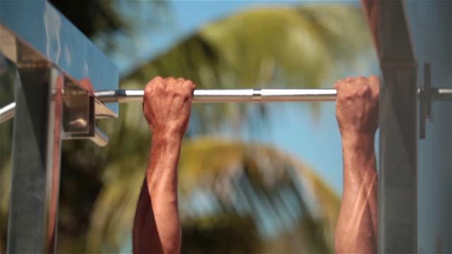 vídeos de stock e filmes b-roll de athletic brazilian man does pull-ups on copacabana beach - puxar
