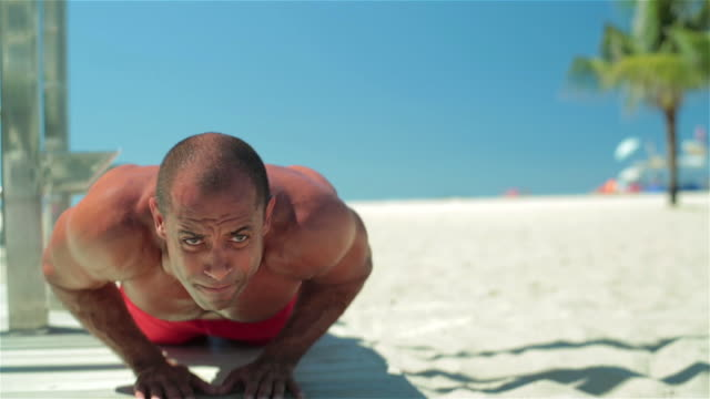 vídeos de stock, filmes e b-roll de athletic brazilian man does push-ups on copacabana beach - atividade