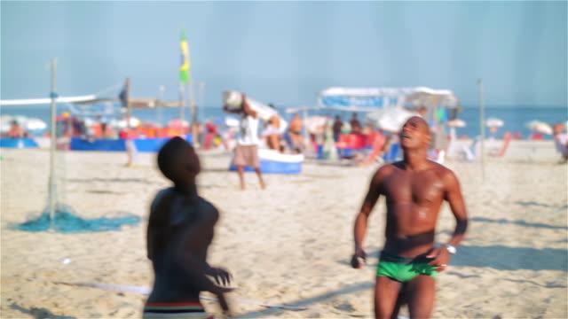 athletic brazilian players pass, set, and head soccer ball over net in beach footvolley match - internationaler fußball stock-videos und b-roll-filmmaterial