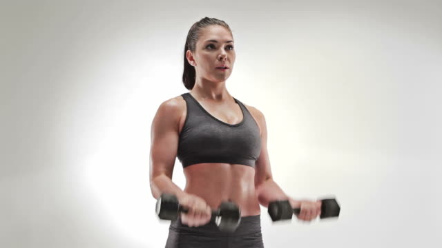 vídeos de stock e filmes b-roll de athletic caucasian woman curling weights both at one time - musculação com peso