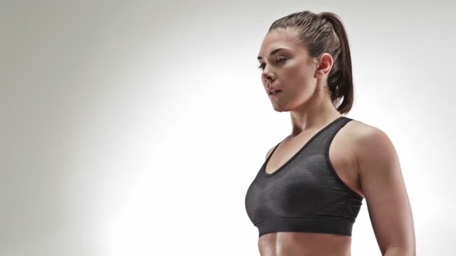Athletic caucasian woman lifting small weights out from the side