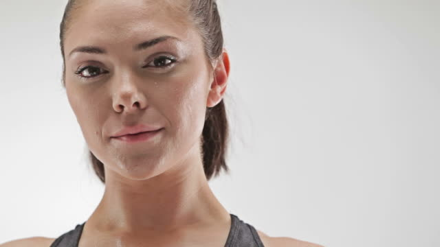 Athletic caucasian woman sweating and looking at camera