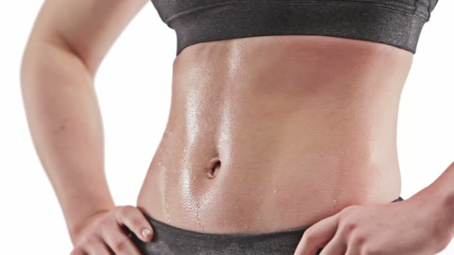 Athletic caucasian woman sweating with hands on hips showing abdomen