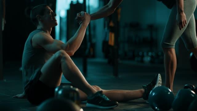 vídeos y material grabado en eventos de stock de atlético pareja saludándose en gimnasio de crossfit - gym