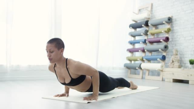 athletic ethnic female doing yoga - yoga studio stock videos & royalty-free footage