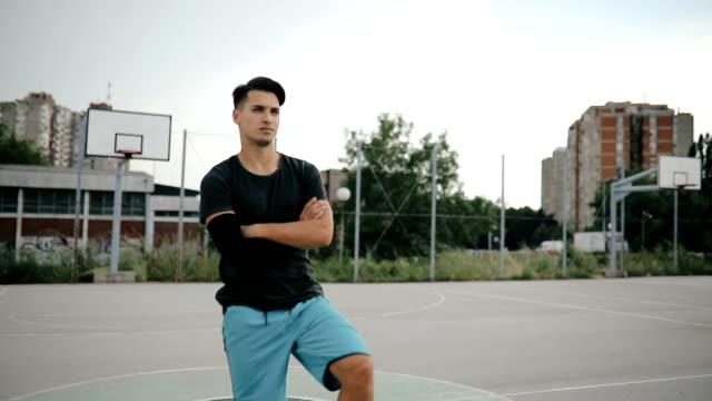 athletische europäischem rang auf einem basketballfeld mit einem ball unter dem arm - korb stock-videos und b-roll-filmmaterial