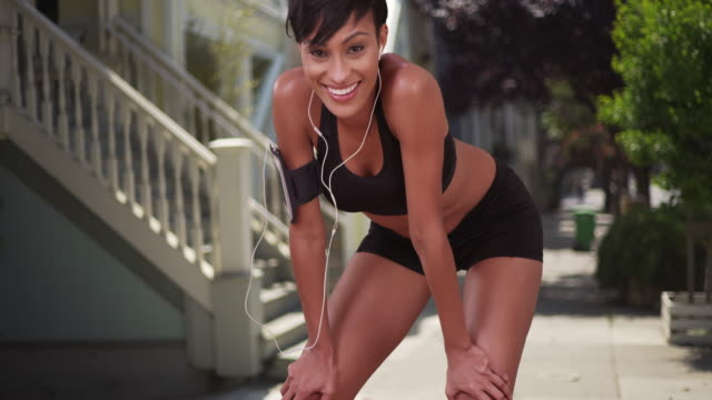 athletic healthy black woman runner resting during jog on city street - african american culture stock videos & royalty-free footage