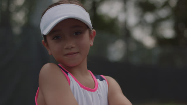 vidéos et rushes de slow mo. cu. athletic little girl hits a tennis ball then crosses her arms and smirks at the camera - concentration