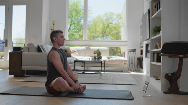 athletic man does a breathing exercise in his home - one young man only stock videos & royalty-free footage