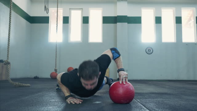 Athletic man doing pushups in one hand.