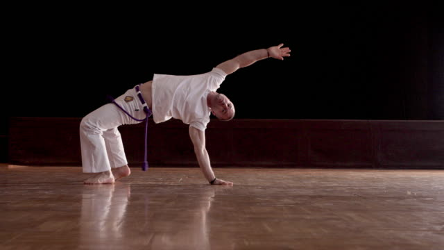 athletic man exercising capoeira in a health club. - acrobatic activity stock videos & royalty-free footage