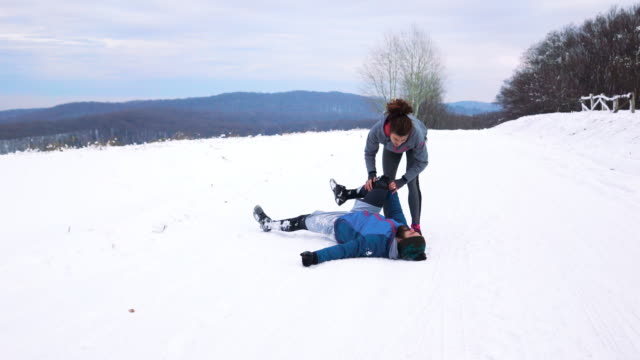 Athletic man experiencing sports injury while running on a snow with his girlfriend.