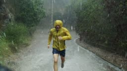 Athletic man jogging in extreme weather condition. Hail and rain