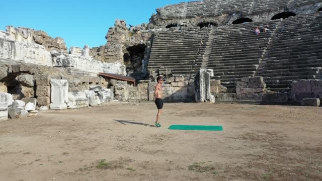vidéos et rushes de entraînement d'homme athlétique sur un amphithéâtre - seulement des jeunes hommes