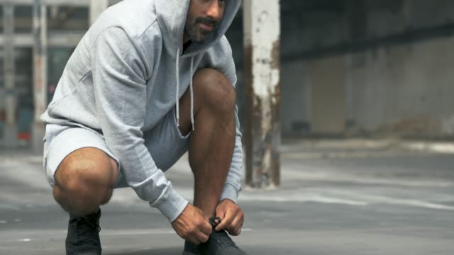 athletic man tying his shoes before a workout - sports clothing stock videos & royalty-free footage