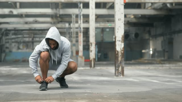 athletic man tying his shoes before a workout - handsome people stock videos & royalty-free footage