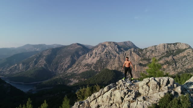 athletic man with a sporting body exercising at great height in front of the huge mountains - bodyweight training stock videos & royalty-free footage