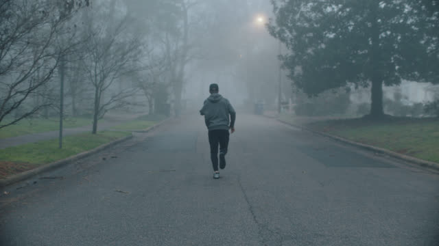 slo mo athletic man with arm amputation runs confidently along a residential road in the early morning - sportsperson stock videos & royalty-free footage