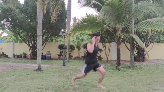stockvideo's en b-roll-footage met atletische volwassen man treinen springen lunges thuis tuin als gevolg van de isolatie voor covid 19 pandemie - oefeningen met lichaamsgewicht