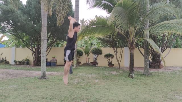 stockvideo's en b-roll-footage met atletische volwassen man treinen springen squat bij huis tuin vanwege de isolatie voor covid 19 pandemie - oefeningen met lichaamsgewicht
