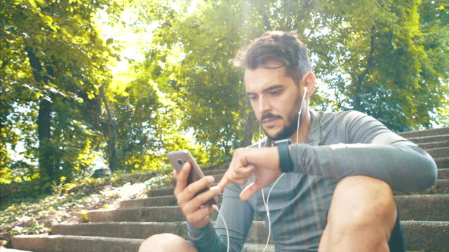 athletic men using his mobile phone. - listening stock videos & royalty-free footage