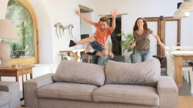 vídeos y material grabado en eventos de stock de madre atlética y niños pequeños saltando sobre la parte posterior del sofá - de origen español o portugués