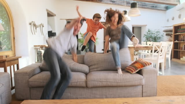 vídeos de stock e filmes b-roll de athletic mother and young children jumping over back of sofa - sofá