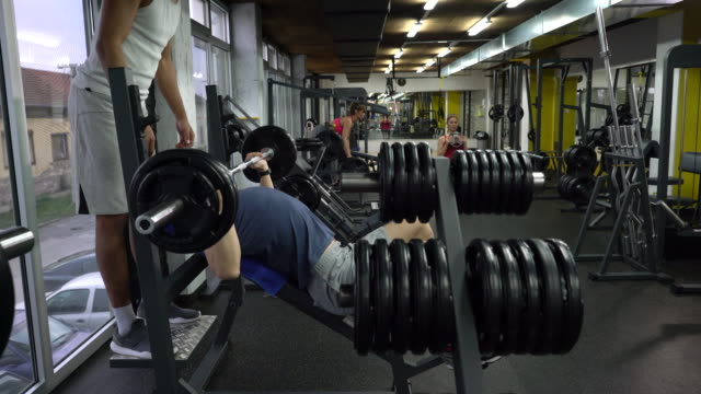 athletic people lifting weights and exercising in a gym. - barbel stock videos and b-roll footage