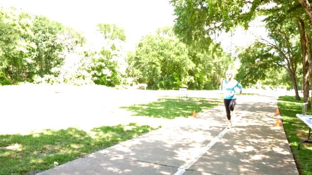 アスレチックシニア女性スプリントを仕上げラインにレース - 女子トラック競技点の映像素材/bロール