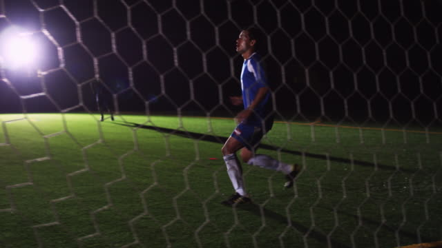 vídeos de stock, filmes e b-roll de slo mo. athletic soccer player receives a pass and kicks the ball past the goalie to score at a nighttime match - passe de bola