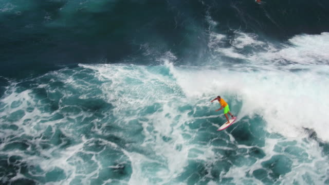 Athletic surfer catches big wave and rides it all the way back to shore