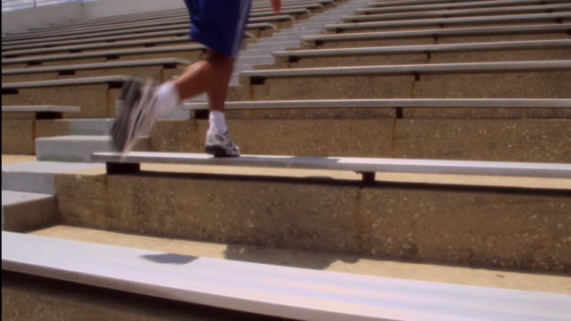 SLO MO. Athletic sweaty man with a muscular build runs quickly up a set of stadium bleachers