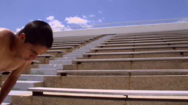 slo mo. athletic sweaty man with a muscular build stands at the bottom of the bleachers of a stadium catching his breath then runs quickly up the bleachers to the top - inhaling stock videos & royalty-free footage