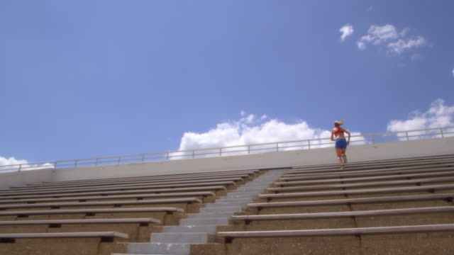 slo mo. athletic sweaty woman with a muscular build runs quickly up a set of stadium bleachers and stops at the top to look around at the view - スポーツマン点の映像素材/bロール