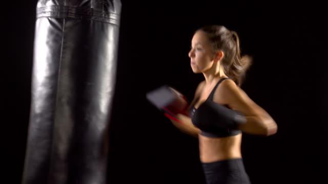 vídeos de stock, filmes e b-roll de mulher atlética boxe saco de pancada - posição de combate