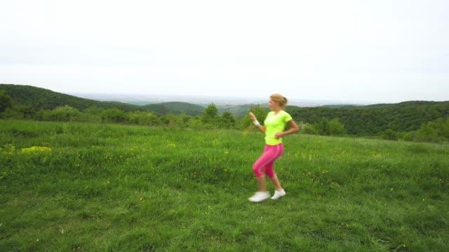 stockvideo's en b-roll-footage met sportieve vrouw vieren tijdens het gebruik in de natuur en haar timing met een stopwatch meten. - menselijke arm