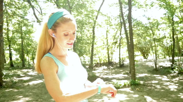 athletic woman checking fitbit before running off road in park - headband stock videos & royalty-free footage
