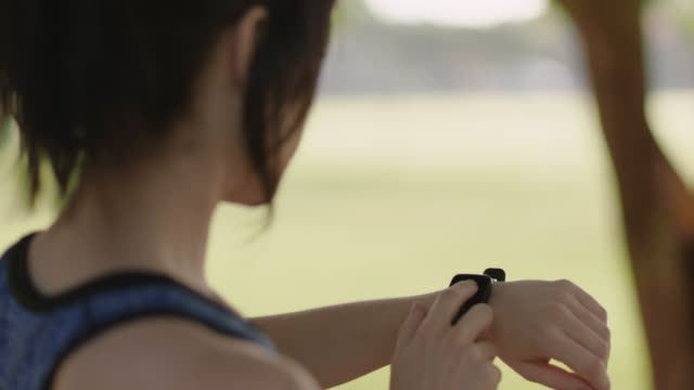 athletic woman checks her smart watch before her morning run - smartwatch video stock e b–roll