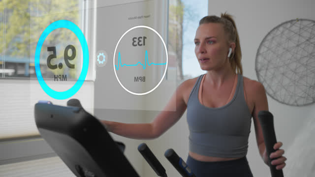 athletic woman controls the speed of her elliptical machine while working out - internet of things stock videos & royalty-free footage
