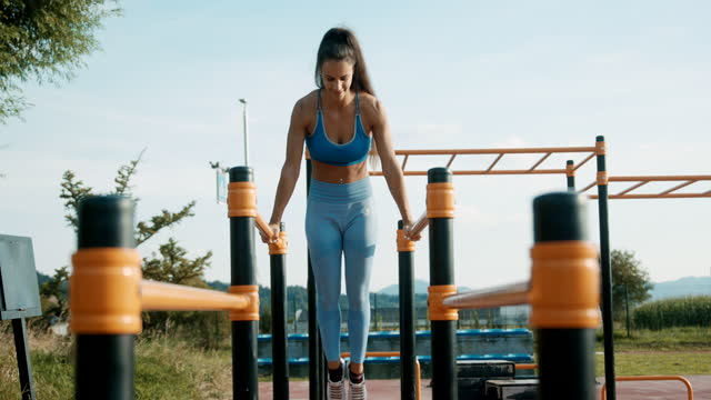 slo mo athletic woman doing exercises on the parallel bars - bodyweight training stock videos & royalty-free footage