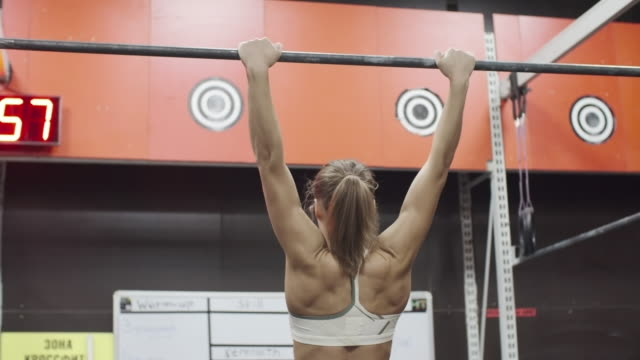 Athletic woman doing pull-ups