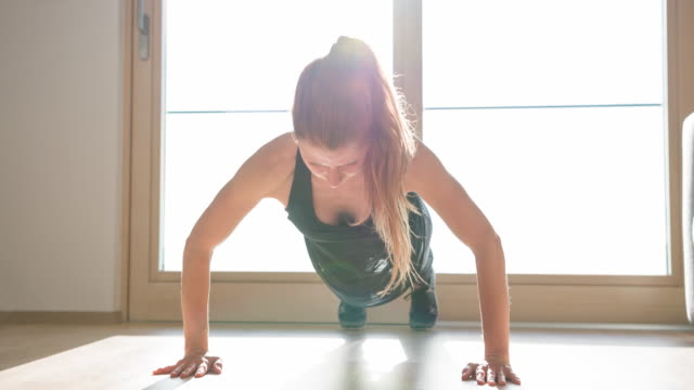 athletic woman doing push-ups at home - postura video stock e b–roll