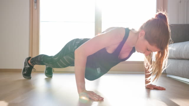 athletic woman doing push-ups at home - home interior stock videos & royalty-free footage