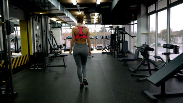 athletic woman entering a gym and exercising on lateral pull-down weights exercise machine. - lateral pull down weights stock videos & royalty-free footage