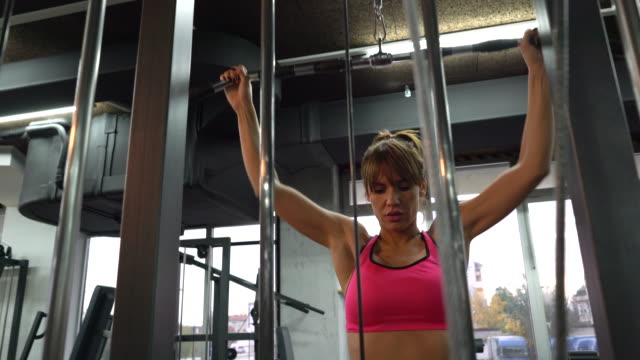 athletic woman exercising on lateral-pull down weight machine in a gym. - lateral pull down weights stock videos & royalty-free footage