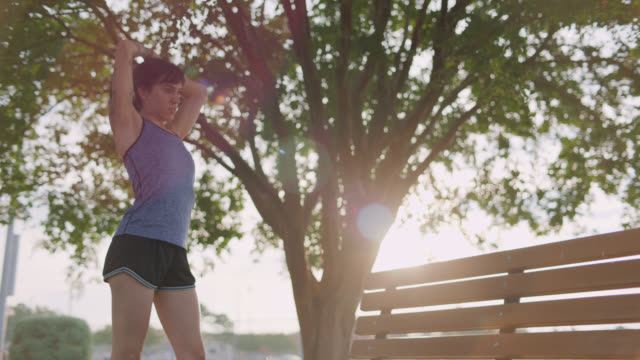 vídeos de stock e filmes b-roll de athletic woman jogs in place, puts her hair into a ponytail and checks her smart watch before her morning run - fim